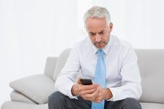 Elegante reife Geschäftsmannversenden von sms-nachrichten zu Hause Lizenzfreie Stockfotografie