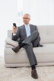 Elegante reife Geschäftsmannversenden von sms-nachrichten zu Hause Stockfotografie
