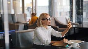 Elegante rijpe blonde dame die op smartphone spreken die videogesprek in koffie maken stock footage