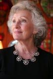 Elegante rijpe vrouw die een zilveren halsband draagt Stock Foto