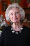 Elegante rijpe vrouw die een zilveren halsband draagt Stock Foto's