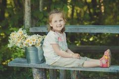 Elegante rubio lindo del niño de la chica joven vestido en la camisa blanca y los pantalones cortos que se sientan en el banco de Foto de archivo libre de regalías