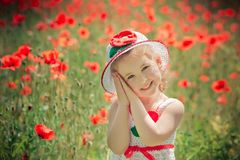 Elegante rubio lindo del niño de la chica joven vestido en el vestido enganchado hecho a mano blanco que lleva la presentación su Fotografía de archivo libre de regalías
