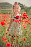 Elegante rubio lindo del niño de la chica joven vestido en el vestido enganchado hecho a mano blanco que lleva la presentación su Fotos de archivo libres de regalías