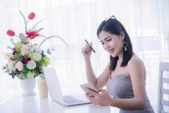 ` Elegante s de la muchacha usando el teléfono elegante y trabajo en el ordenador portátil, tiempo feliz Imagen de archivo libre de regalías