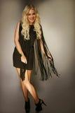 Elegante schöne blonde Frau in einem schwarzen Kleid Stockfotos