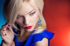 Elegante Schönheiten blond mit den roten Lippen in einem blauen Kleid im Studio Lizenzfreie Stockfotografie