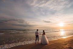 Elegante schitterende bruid en bruidegom die op oceaanstrand tijdens zonsondergangtijd lopen Romantische gangjonggehuwden op trop royalty-vrije stock fotografie
