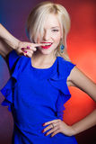 Elegante Schönheiten blond mit den roten Lippen in einem blauen Kleid im Studio Lizenzfreies Stockfoto