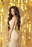 Elegante sexy donkerbruine vrouw in goud Het portret van de schoonheidsmanier van Stock Foto