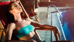 Elegante sexy vrouw in de witte bikini op het zon-gelooide slanke en goed gevormde lichaam stock foto's