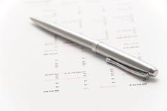 Elegante silberne Feder auf Finanzpapieren Stockfotografie