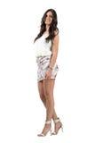 Elegante sinnliche lange Schönheit des gewellten Haares im kurzen Kleid, das an der Kamera lächelt Stockfotos