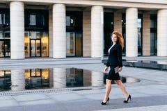 Elegante slanke vrouw in zwart kostuum en high-heeled schoenen, die tablet in handen houden die voor het werk gaan Onderneemster  stock afbeelding