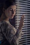 Elegante stijl donkerbruine vrouw die door jaloezie kijken Royalty-vrije Stock Foto