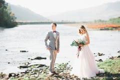 Elegante stilvolle glückliche blonde Braut und herrlicher Bräutigam auf dem Hintergrund von einem schönen Fluss in den Bergen stockbild