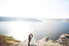 Elegante stilvolle glückliche Hochzeitspaare, Braut, herrlicher Bräutigam auf dem Hintergrund von Meer und Himmel Lizenzfreie Stockfotografie