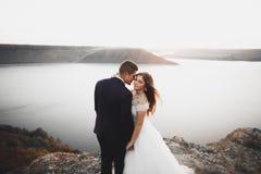 Elegante stilvolle glückliche Hochzeitspaare, Braut, herrlicher Bräutigam auf dem Hintergrund von Meer und Himmel stockfotos