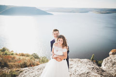 Elegante stilvolle glückliche Hochzeitspaare, Braut, herrlicher Bräutigam auf dem Hintergrund von Meer und Himmel lizenzfreies stockbild