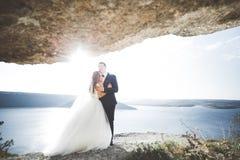 Elegante stilvolle glückliche Hochzeitspaare, Braut, herrlicher Bräutigam auf dem Hintergrund von Meer und Himmel Lizenzfreie Stockbilder