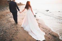 Elegante stilvolle gl?ckliche Hochzeitspaare, Braut, herrlicher Br?utigam auf dem Hintergrund von Meer und Himmel stockfotografie