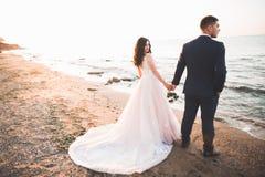 Elegante stilvolle gl?ckliche Hochzeitspaare, Braut, herrlicher Br?utigam auf dem Hintergrund von Meer und Himmel stockfotos