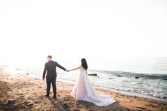 Elegante stilvolle gl?ckliche Hochzeitspaare, Braut, herrlicher Br?utigam auf dem Hintergrund von Meer und Himmel stockfoto
