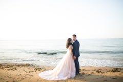 Elegante stilvolle gl?ckliche Hochzeitspaare, Braut, herrlicher Br?utigam auf dem Hintergrund von Meer und Himmel lizenzfreie stockfotografie
