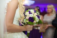Elegante stilvolle herrliche blonde Braut mit Blumenstrauß im restau Lizenzfreie Stockfotos