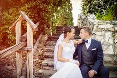 Elegante stilvolle junge Braut und Bräutigam, die auf der Treppe im Park sitzt stockfoto