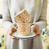 Elegante thee of koffiekoppen en schotels in de handen van vrouwen De vrouw houdt een ceramische schotel stock afbeeldingen