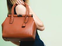 Elegante uitrusting Bruine leerzak in vrouwelijke hand Stock Foto's