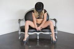Elegante und recht blonde Frau, die auf einem Sofa sitzt Stockfoto