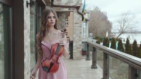 Elegante violistgangen en spelen op viool bij huis stock footage