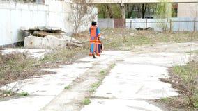 Elegante volwassen vrouwengangen langs een weg in de afval-grond stock footage