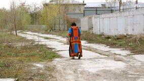 Elegante volwassen vrouwengangen langs een weg in de afval-grond stock videobeelden