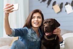 Elegante vrolijke dame en haar huisdier het stellen voor een schot Stock Afbeelding