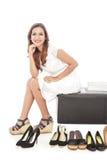 elegante vrouw die en naast paren schoenen glimlachen zitten Royalty-vrije Stock Foto