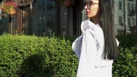 Elegante vrouw die in langzame motie dichtbij shop-windows lopen stock footage