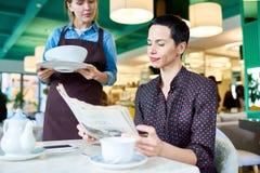 Elegante Vrouw die op Voedsel in Koffie wachten stock foto