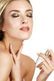 Elegante vrouw die parfum op haar lichaam toepassen stock afbeeldingen