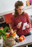 Elegante vrouw die zich in keukenholding het winkelen lijst en contant geld bevinden royalty-vrije stock afbeeldingen