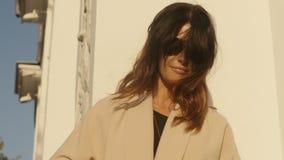 Elegante vrouw in laag en zonnebril stock videobeelden