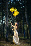 Elegante vrouw in lange kleding met ballons in hout royalty-vrije stock fotografie