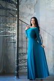 Elegante vrouw in luxe lange violette kleding die zich dichtbij treden bevinden Stock Foto