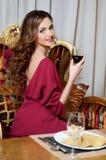 Elegante vrouw met een wijnglas bij slim restaurant Stock Foto