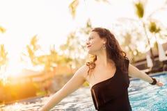 Elegante vrouw met volkomen het gelooide lichaam stellen in zwembad bij luxueus hotel Royalty-vrije Stock Fotografie