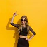 Elegante Vrouw op Gele Achtergrond die benadrukken Royalty-vrije Stock Afbeeldingen