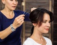 Elegante vrouw in schoonheidszaal De kapper doet kapsel in de vorm van grote krul Het kapsel van het conceptenhuwelijk stock afbeeldingen