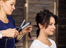Elegante vrouw in schoonheidszaal De kapper doet kapsel in de vorm van grote krul Het kapsel van het conceptenhuwelijk royalty-vrije stock fotografie